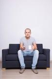 Homem considerável novo que senta-se no sofá e na tevê de observação com o copo de t Foto de Stock Royalty Free
