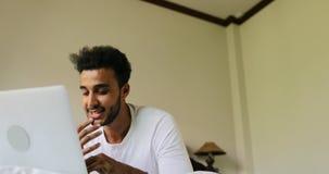 Homem contemplativo que usa o laptop que encontra-se na manhã do quarto de Guy Type Chatting Online In do hispânico da cama video estoque