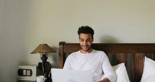 Homem contemplativo que usa o laptop que senta-se na manhã do quarto de Guy Type Chatting Online In do hispânico da cama filme