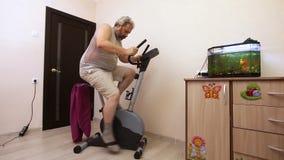 Homem contratado na bicicleta de exercício na sala filme