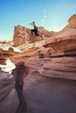 Homem corajoso que salta sobre o penhasco na garganta foto de stock royalty free