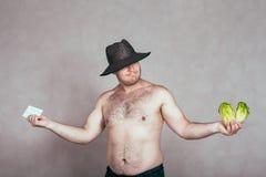 Homem corpulento despido indeciso com fármacos e vegetabl Fotos de Stock