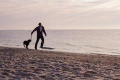 homem corrido com o cão na praia Imagem de Stock Royalty Free