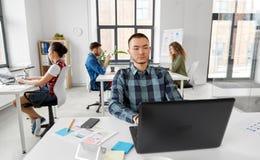 Homem criativo com o portátil que trabalha no escritório imagem de stock royalty free