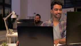Homem criativo com o portátil que trabalha no escritório da noite vídeos de arquivo