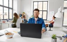 Homem criativo de sorriso com o portátil que trabalha no escritório imagens de stock royalty free