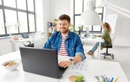 Homem criativo de sorriso com o portátil que trabalha no escritório foto de stock