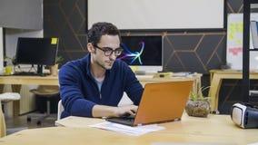 Homem criativo nos vidros usando o portátil no local de trabalho fotografia de stock royalty free