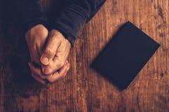 Homem cristão que reza com as mãos cruzadas imagem de stock