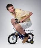 Homem curioso no crianças \ 'bicicleta de s Fotos de Stock Royalty Free