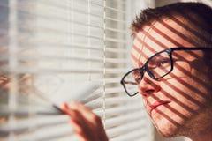 Homem curioso que olha através de um jalousie fotografia de stock royalty free