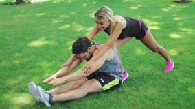 Homem da aptidão da ajuda do instrutor do esporte da mulher que estica os pés no parque do verão vídeos de arquivo