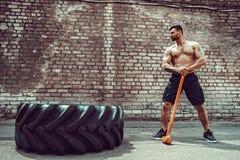 Homem da aptidão do esporte que bate o pneu da roda com treinamento de Crossfit do pequeno trenó do martelo imagem de stock royalty free