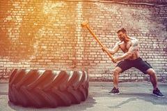 Homem da aptidão do esporte que bate o pneu da roda com treinamento de Crossfit do pequeno trenó do martelo fotos de stock royalty free
