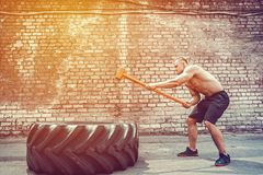 Homem da aptidão do esporte que bate o pneu da roda com treinamento de Crossfit do pequeno trenó do martelo fotos de stock