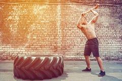 Homem da aptidão do esporte que bate o pneu da roda com treinamento de Crossfit do pequeno trenó do martelo foto de stock royalty free