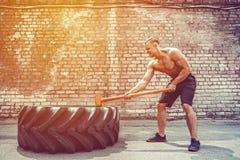 Homem da aptidão do esporte que bate o pneu da roda com treinamento de Crossfit do pequeno trenó do martelo fotografia de stock royalty free