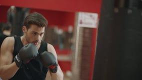 Homem da aptidão nas luvas que fazem sopros no saco do combate no treinamento do encaixotamento no gym filme