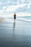Homem da aptidão que corre na praia Corredor que movimenta-se durante o exercício exterior imagem de stock royalty free