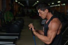 Homem da aptidão que exercita com esticão da faixa no gym Homem muscular dos esportes que dá certo com elástico imagem de stock
