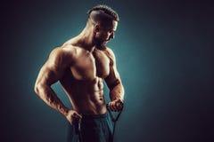 Homem da aptidão que exercita com esticão da faixa Homem muscular dos esportes que exercita com elástico elástico Dar certo do in imagens de stock