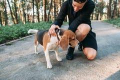 Homem da aptidão no sportswear com seu cão na floresta Fotos de Stock