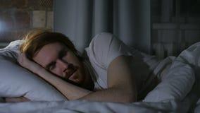 Homem da barba do ruivo que encontra-se na cama e que dorme na sala escura na noite filme