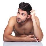 Homem da beleza que risca sua cabeça e que olha acima a seu lado Fotos de Stock Royalty Free