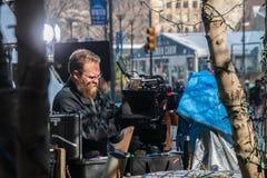 Homem da câmera que ajusta sua câmera no local do película de um anúncio publicitário imagens de stock