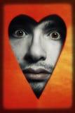 Homem da face que perscruta do furo em heart-shaped fotografia de stock royalty free