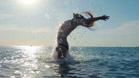Homem da força que banha-se no mar que joga o cabelo longo cercado espirrando no movimento lento do por do sol filme