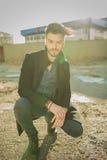 Homem da forma que senta-se perto das fábricas velhas Fotografia de Stock Royalty Free
