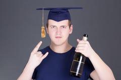 Homem da graduação com diploma e garrafa do álcool fotografia de stock royalty free