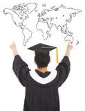 Homem da graduação que veste um barrete e um ponto ao mundo fotos de stock royalty free