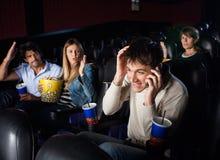 Homem da gritaria dos espectadores que usa o telefone celular dentro Foto de Stock Royalty Free