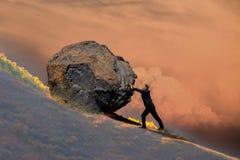Homem da Idade Média que empurra uma rocha de queda imagem de stock