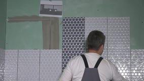 Homem da Idade Média que telha a parede no banheiro video estoque