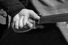 Homem da mão marcado para segurar a peça larga da espada da empunhadura da faca do site tonificado close-up da base do projeto do fotografia de stock