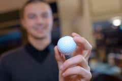 Homem da mão que guarda a bola de golfe Imagem de Stock Royalty Free