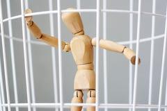 Homem da madeira em uma gaiola fotografia de stock royalty free