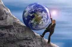 Homem da metáfora de Sisyphus que rola a bola enorme da rocha da terra acima do monte Foto de Stock