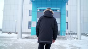Homem da opinião da parte traseira em caminhadas do revestimento à entrada do centro do escritório video estoque