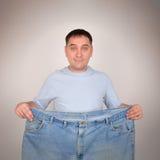 Homem da perda de peso que guarda calças grandes fotos de stock royalty free