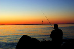 Homem da pesca no por do sol da beira do lago Imagem de Stock Royalty Free