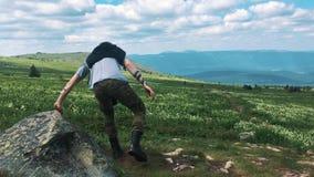 Homem da pose da vitória na parte superior do monte, sentada para baixo ao resto após uma estrada dura Trajeto da montanha filme