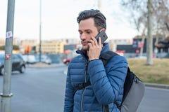Homem da rua novo do negócio que fala em um telefone celular e em um casaco azul imagem de stock