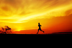 Homem da silhueta que movimenta-se no por do sol Imagem de Stock