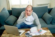 Homem da virada no esforço que paga a cartão de crédito débitos em linha e que conta a finança com papéis do portátil e de banco imagens de stock