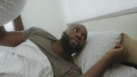 Homem da virada que encontra-se na cama na manhã Cabeça de coberta adulta africana com descanso filme