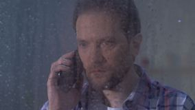 Homem da virada que fala no telefone, recebendo más notícias no dia chuvoso, morte relativa video estoque